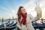 Happy woman traveler taking selfie on embankment in Venice