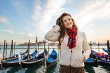 Happy young woman traveler standing on embankment in Venice