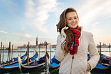 Dreamy woman traveler standing on embankment in Venice, Italy