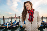 Young woman traveler standing on embankment in Venice, Italy