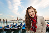 Portrait of happy woman traveler on embankment in Venice, Italy