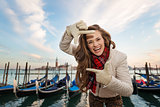 Woman traveler framing with hands on embankment in Venice, Italy