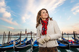 Dreamy young woman traveler standing on embankment in Venice