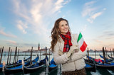 Woman traveler with Italian flag standing on embankment, Venice
