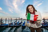 Woman traveler showing Italian flag on embankment in Venice