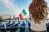 Closeup on Italian flag in hands of woman traveler in Venice