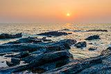 bright orange sun over the sea and rocky shore