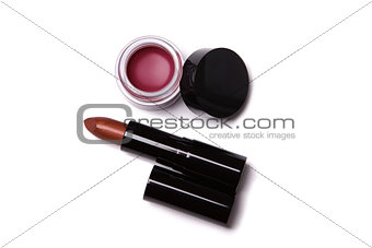 Top view of metallic red lipstick and lip gloss in jar