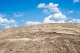 Sandy dirt hill with tracks against clouds and sky