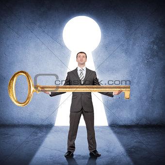 Man in suit holding huge gold key