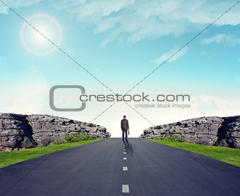 Man in suit on road with mountains