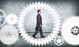 Businessman walking in cog wheel, side view