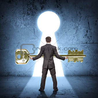 Man holding huge gold key, rear view