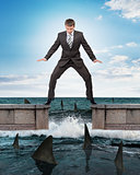 Businessman standing above sharks