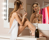 woman doing make-up and drinking champagne