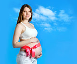 Beautiful pregnant woman in the blue sky background