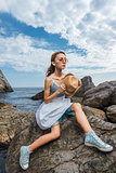 Young teen posing on stones at sea fashion photoshoot