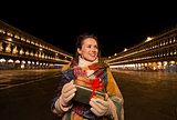 Happy woman with Christmas gift box on Piazza San Marco, Venice
