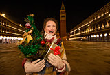 Woman with Christmas tree and gift standing on Piazza San Marco