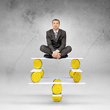 Businessman sitting on balance with gold coins