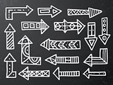 Hand drawn arrow icons set on black chalk board.