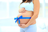 woman holds her baby bump,