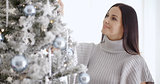 Pretty young woman decorating her Christmas tree