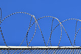 Fence with a barbed wire against the blue sky.