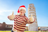 Woman in Santa hat showing thumbs up near Leaning Tour of Pisa