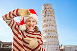 Woman in Santa hat framing with hands near Leaning Tour of Pisa