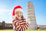 Smiling woman in Santa hat pointing on Leaning Tour of Pisa