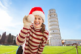 Woman playing with Santa hat in front of Leaning Tour of Pisa