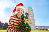 Woman in Santa hat with Christmas tree near Leaning Tour, Pisa