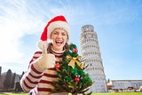 Woman with Christmas tree showing thumbs up near Leaning Tour