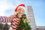 Woman with Christmas tree taking selfie near Leaning Tour