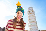 Happy woman in Christmas tree hat near Leaning Tour of Pisa