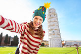 Woman in Christmas tree hat taking selfie in Pisa