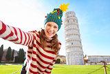 Woman in Christmas tree hat taking selfie in Pisa