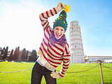 Woman make fun of Christmas tree hat near Leaning Tour of Pisa