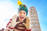 Woman in Christmas tree hat shouting in front of Leaning Tour