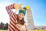 Woman in Christmas tree hat framing near Leaning Tour of Pisa