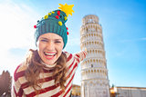 Woman in Christmas tree hat pointing on Leaning Tour of Pisa
