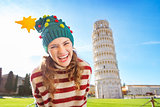Merry woman in Christmas tree hat near Leaning Tour of Pisa