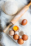 Dough, rolling pin and a tray of eggs.