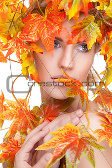 Beautiful woman wrapped in autumn leafs