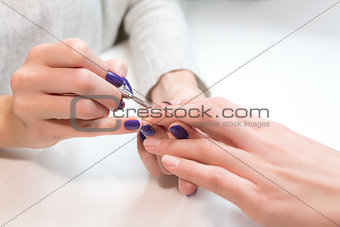 Beautician remove cuticle from ring finger client