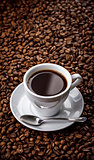 Cup with fragrant coffee drink on beans background