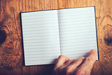 Man flipping pages of blank notebook