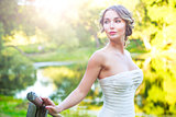 Stylish Young Bride Outdoors at Green Nature Background. Toned Photo.