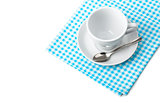 White coffee cup with saucer and spoon tableware on blue chequered napkin